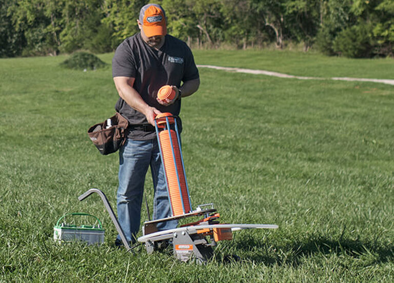 Man loading traps into Champion Workhorse Electronic Trap in field
